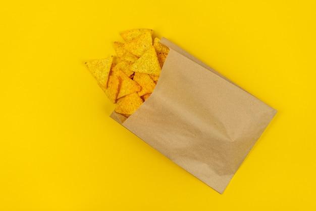 Nachos chips en una bolsa de papel ecológica, comida rápida.