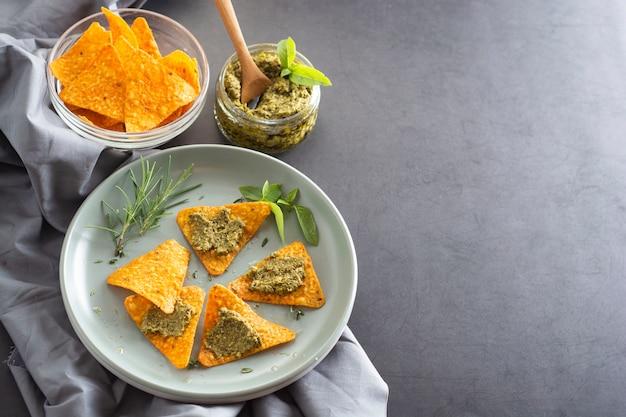 Nachos chips o chips mexicanos de maíz con guacamole, pesto pasta comida saludable merienda, copyspace