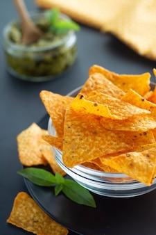 Nachos chips o chips mexicanos de maíz en un tazón de vidrio, merienda de alimentos saludables aislados