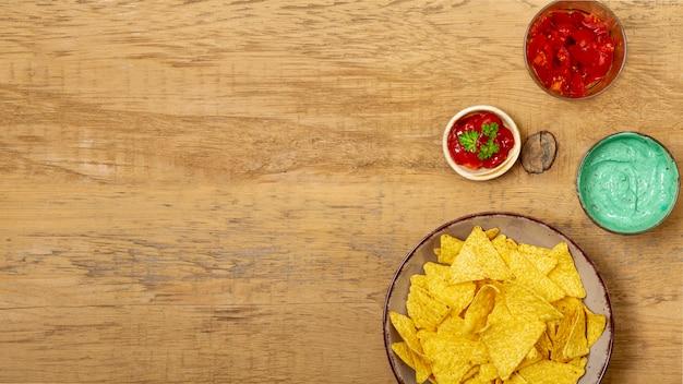Nachos y diferentes salsas orgánicas en mesa de madera