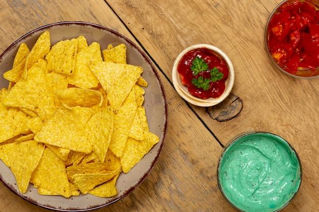 Nachos y diversas salsas orgánicas en mesa de madera colocada