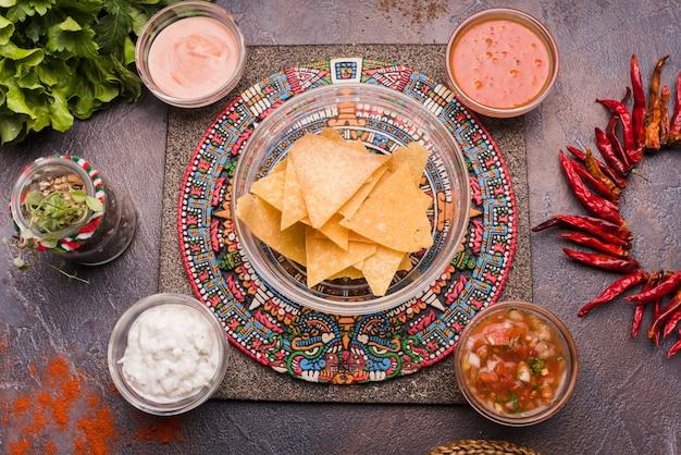 Nachos junto a la pimienta y la salsa en tazones colocados en una bandeja creativa