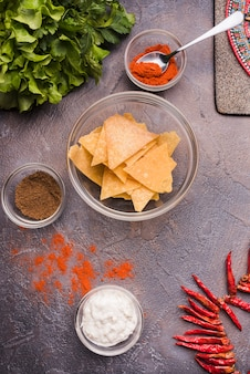 Nachos junto a la pimienta y la salsa en tazones.