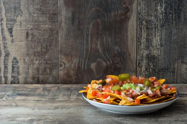 Nachos mexicanos con carne de res, guacamole, salsa de queso, pimientos, tomate y cebolla en placa sobre fondo de madera