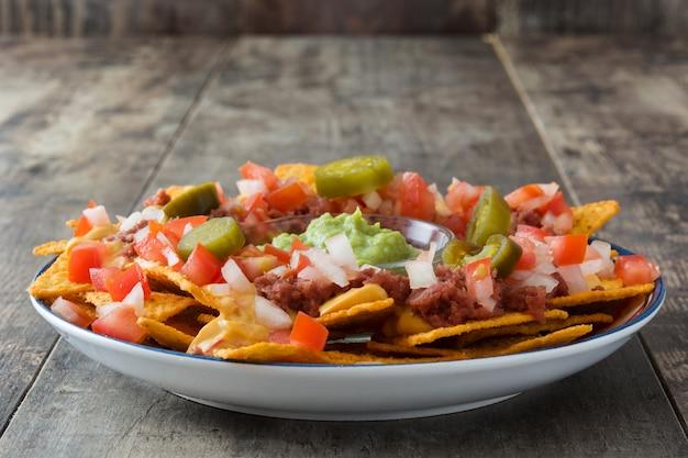 Nachos mexicanos con carne de res, guacamole, salsa de queso, pimientos, tomate y cebolla en plato sobre mesa de madera