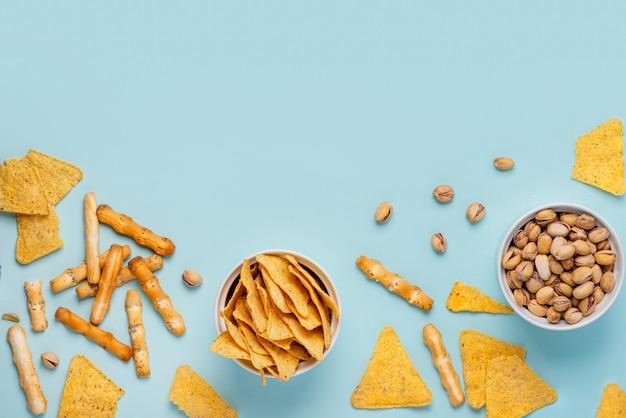 Nachos, pistachos y palitos de queso en tazones blancos sobre fondo azul, vista superior, plano