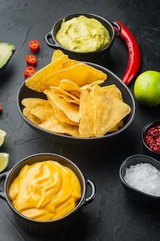 Nachos y salsas de guacamole y queso, sobre mesa negra
