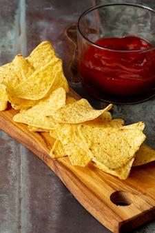 Nachos en tabla de cortar y salsa de tomate en recipiente de vidrio