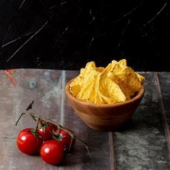 Nachos en tazón y rama de tomates en la mesa