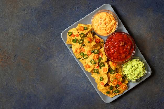 Nachos de tortilla de maíz amarillo mexicano con jalapeño, guacamole, salsa de queso y salsa