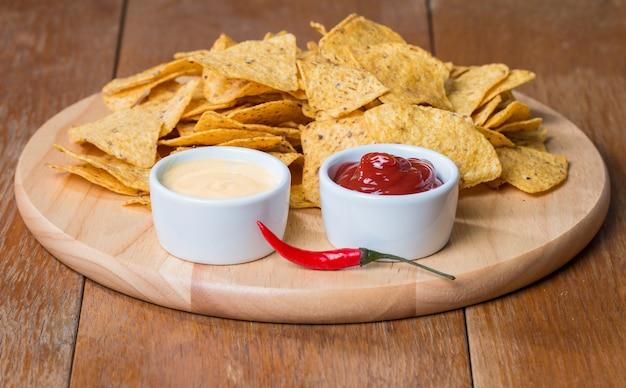 Nachos con varias salsas en mesa de madera