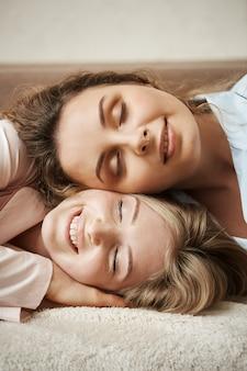 Nada podría separar o romper esta amistad. toma vertical de la linda madre acostada sobre la cabeza de la hija, sonriendo ampliamente, sintiendo unidad y relajándose el fin de semana, teniendo conversaciones íntimas sobre la vida