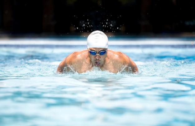 Nadador en gorra y gafas en piscina.