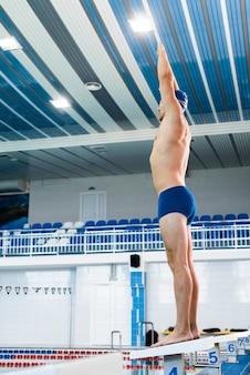 Nadador masculino de ángulo bajo en posición preparada