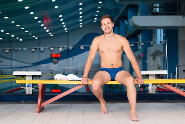 Nadador masculino de ángulo bajo sonriente en descanso