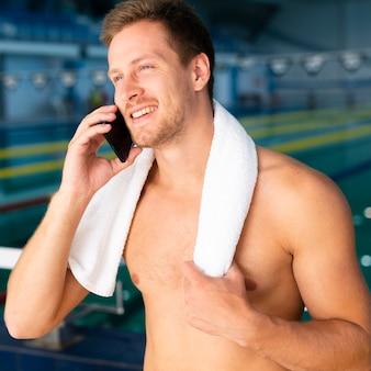 Nadador masculino en la piscina hablando por teléfono