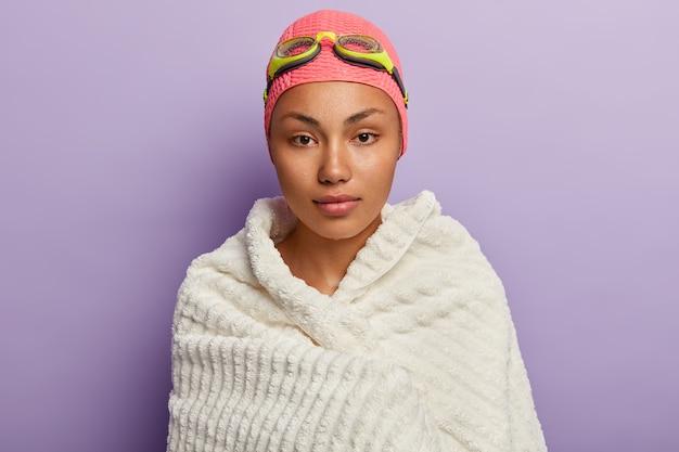 El nadador serio y tranquilo se seca con una toalla blanca suave, se calienta después de practicar la espalda, usa gafas y gorro de natación, mejora sus habilidades, tiene la piel húmeda, está aislada sobre una pared púrpura, se mantiene en forma