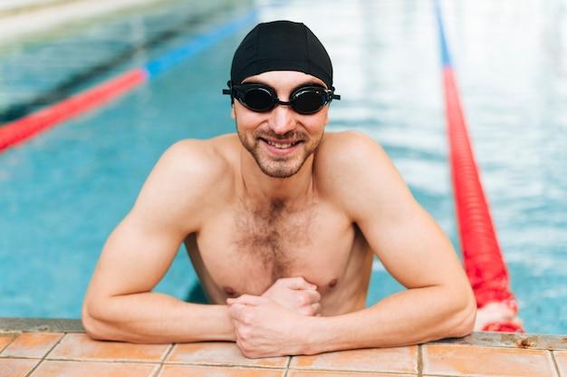 Nadador sonriente de alto ángulo en el borde de la cuenca