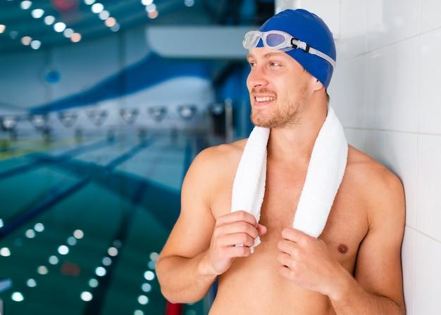 Nadador sosteniendo su toalla y mirando a otro lado