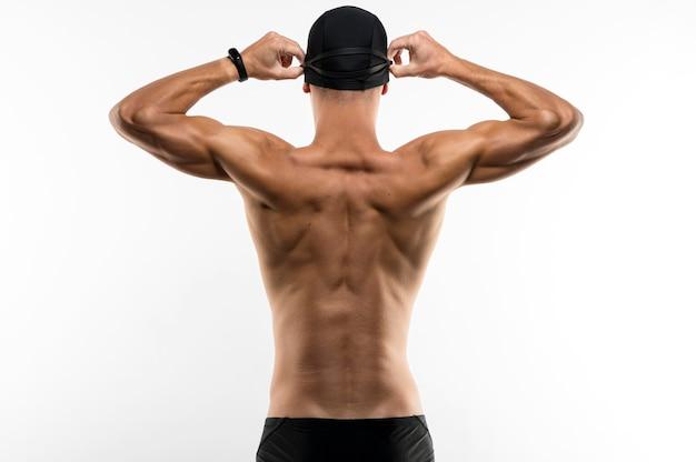 Nadador de tiro medio arreglando su gorra
