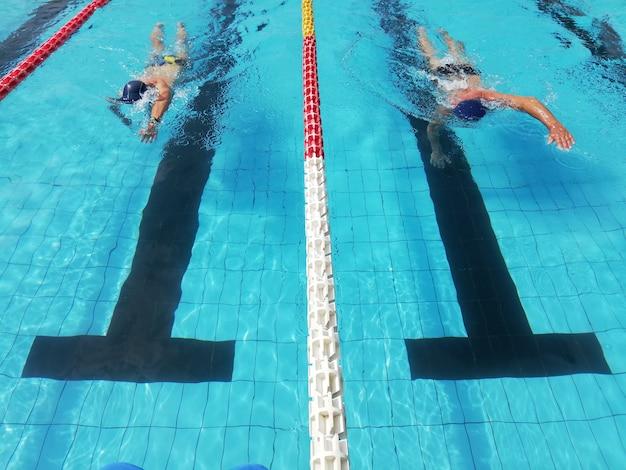 Nadadores en piscina de carril, hombres en agua.