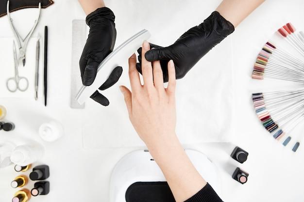 Nail tech limando uñas con lima de uñas. herramientas de manicura profesional.