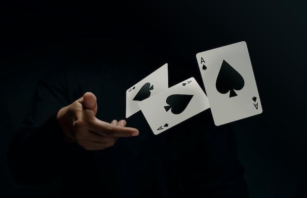 Naipe ace spade. jugador o mago golpea ligeramente y levita la tarjeta de póquer a mano. vista frontal. primer plano y tono oscuro