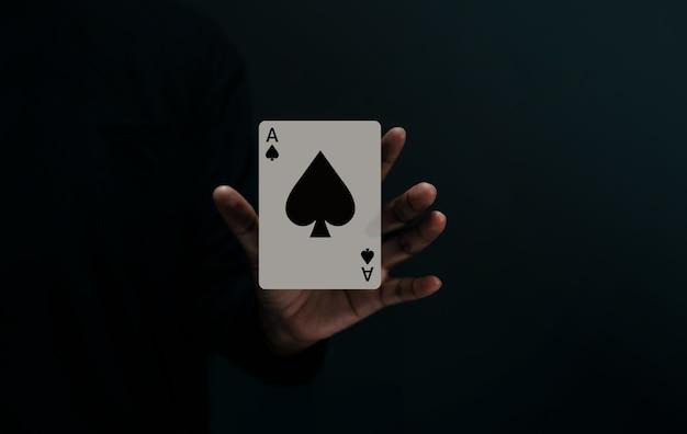 Naipe ace spade. jugador o mago levitando una tarjeta de póquer en la mano. vista frontal. primer plano y tono oscuro