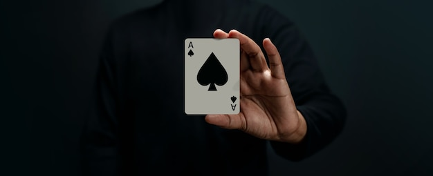 Naipe ace spade. jugador o mago sosteniendo una tarjeta de póquer. vista frontal. primer plano y tono oscuro