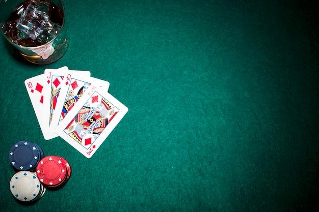 Naipes de escalera real de diamante; fichas de casino y vaso de whisky con cubitos de hielo sobre fondo verde