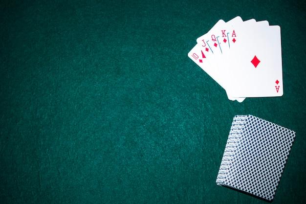 Naipes de escalera real en la mesa de póquer