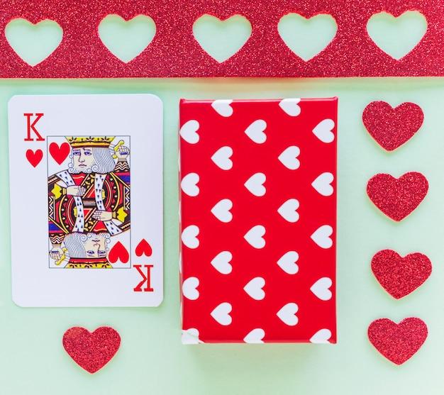 Naipes de rey de corazones con caja de regalo en mesa