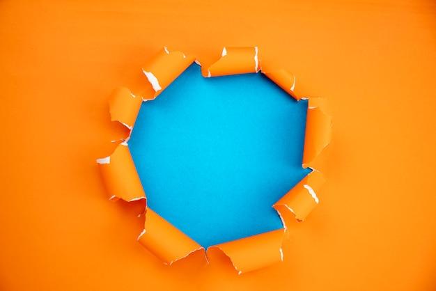 Naranja arrancó papel abierto sobre fondo de papel azul