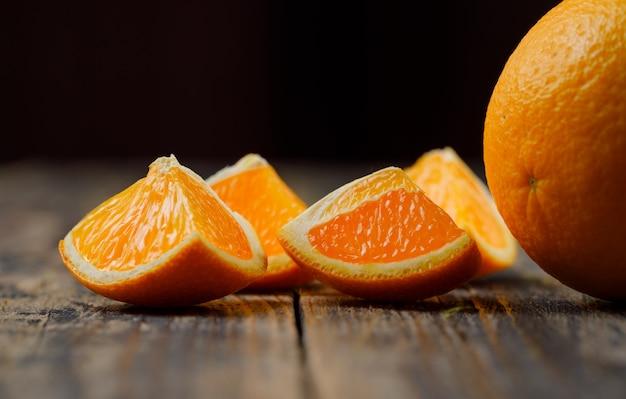Naranja de buen gusto con vista lateral de rodajas en la mesa negra y de madera