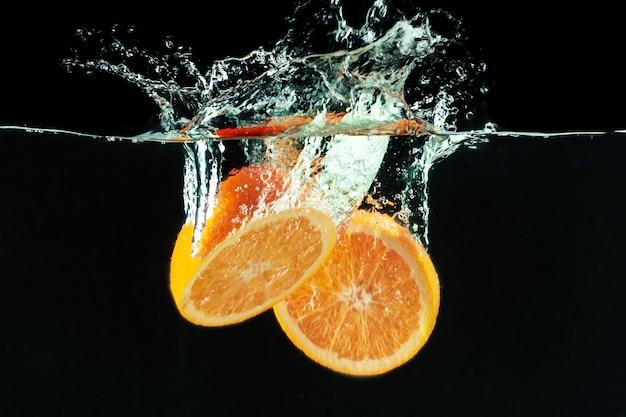 La naranja cae al agua y haciendo salpicaduras.