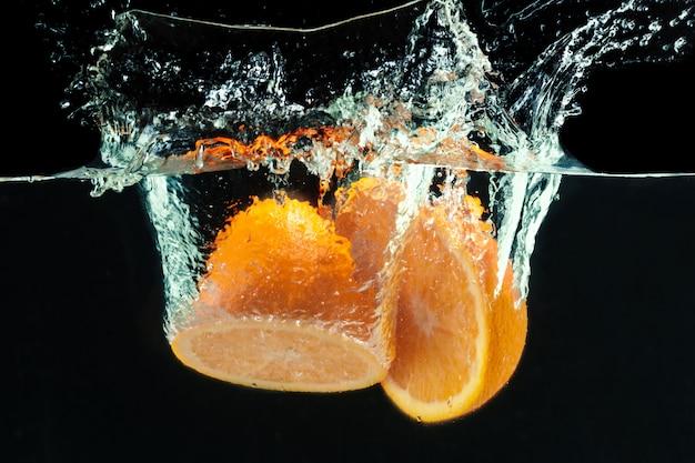 Naranja cae al agua y salpica