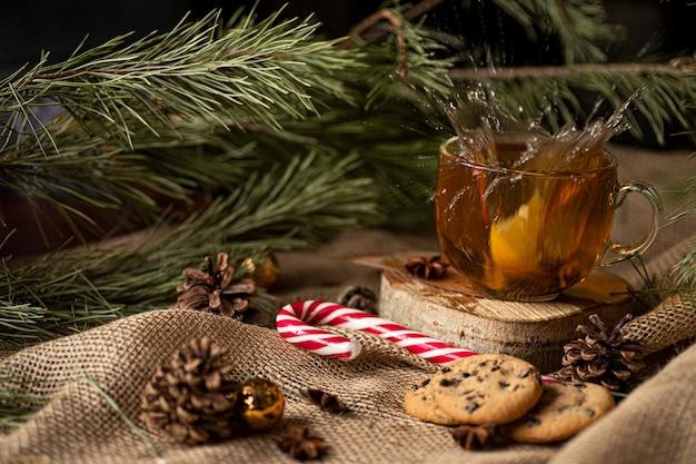 Naranja cae en el té y salpica, junto a galletas y piruletas en un árbol de navidad y conos.