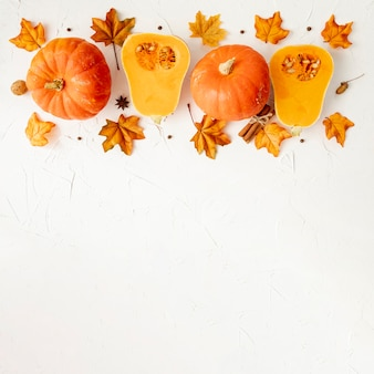 Naranja calabazas en hojas con fondo blanco.