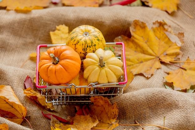 Naranja calabazas y hojas sobre tela de saco arrugado