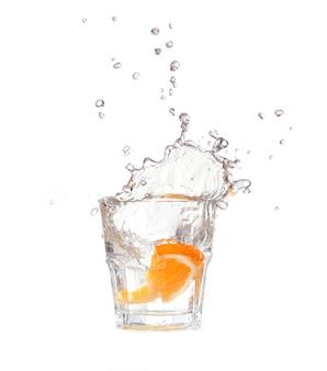 Naranja chapoteando en un vaso de agua sobre fondo blanco.