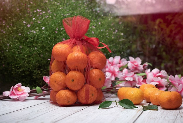 Naranja chino en bolsas rojas sobre mesa de madera exterior