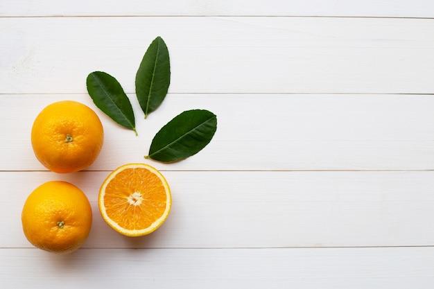 Naranja cítricos y hojas verdes en blanco de madera