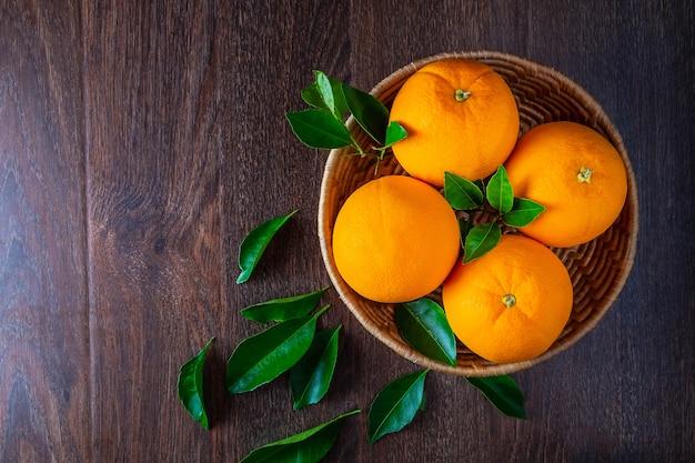 Naranja fresca en la cesta en la vista superior de fondo de madera