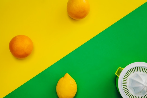 Naranja, limón y exprimidor con espacio para copiar