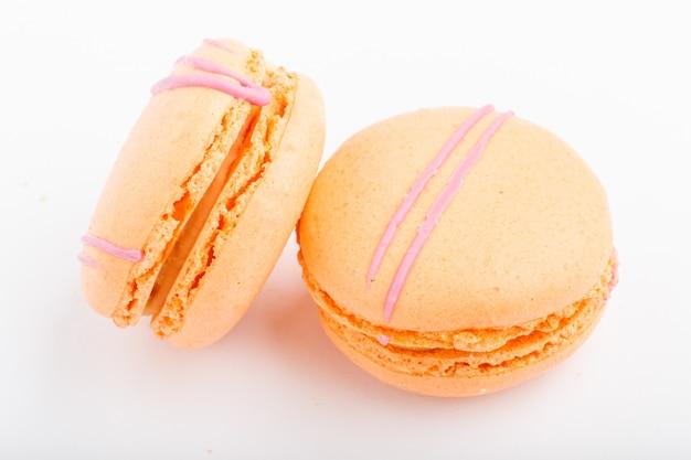 Naranja macarons o pasteles de macarrones aislado sobre fondo blanco.