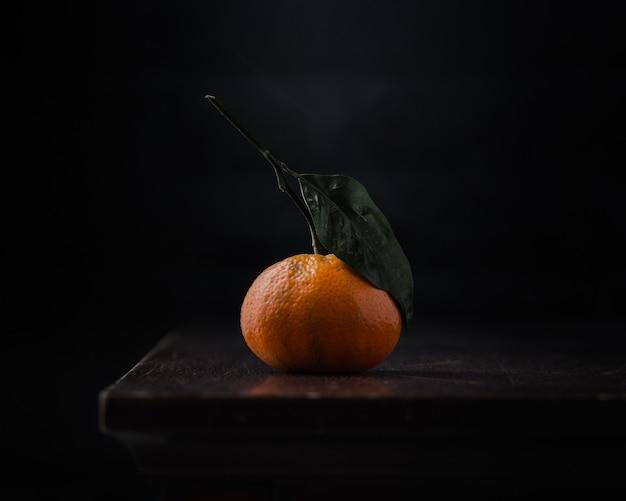 Una naranja en mesa negra