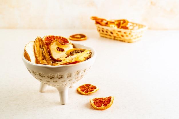 Naranja orgánica, manzana y otras frutas chips en un tazón y una cesta de mesa sobre fondo de color pastel