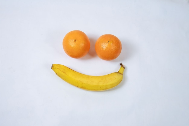 Naranja y plátano, formando un smiley, aislado en blanco. sonrisa. tristeza.