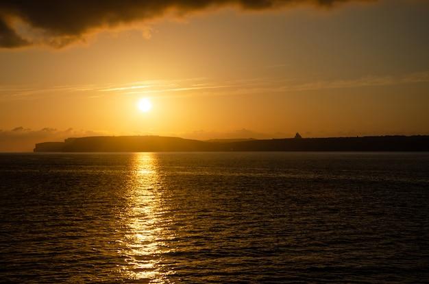 Naranja puesta de sol en el mar en gozo