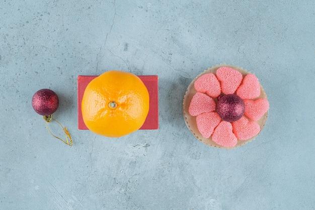 Naranja sobre caja roja junto a una pequeña fuente de mermeladas alrededor de una bola decorativa sobre mármol.